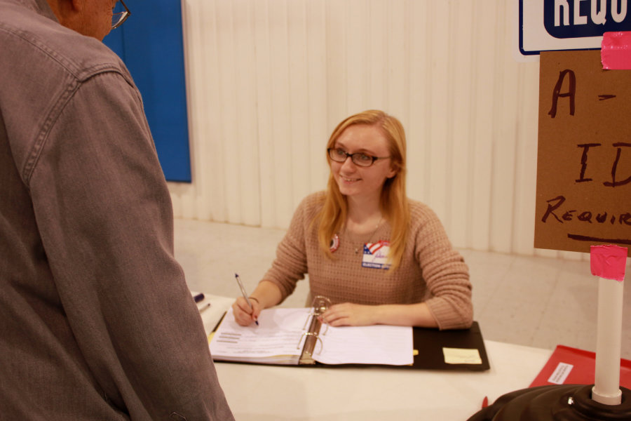Senior Juliana Wall greets a voter as she signs him in the registrar book.  Over 1,030 people came through the doors on Election Day.