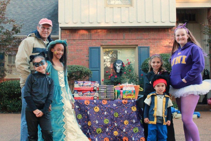 Mr. Williams poses next to his candy table with his grandchildren and their friends.  The kids then later went trick-or-treating in their  costumes.