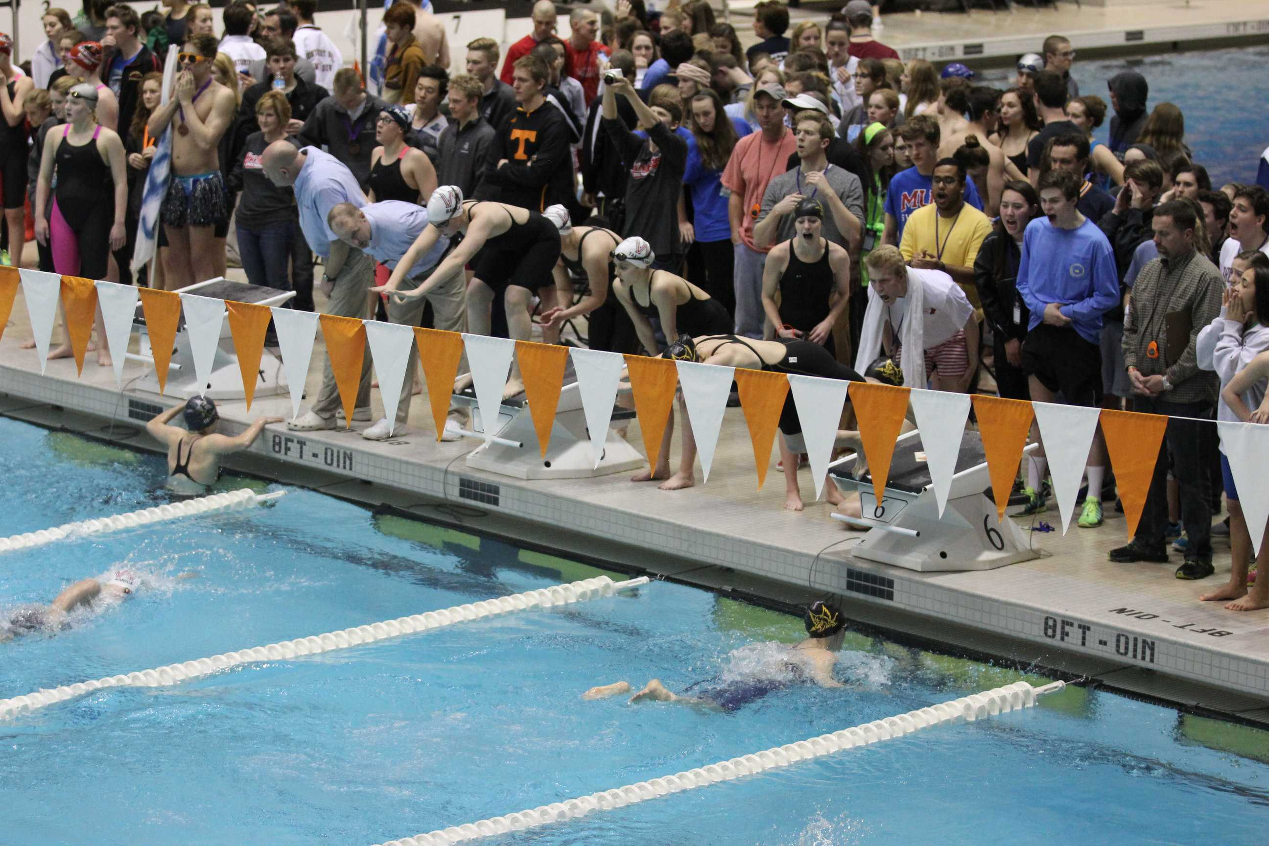 Lexie Marotta dives in after Julia Fogel during a relay while their team cheers them on. A total of seven school records were broken by the Gryphons at the state championships, including Marotta and Fogel's girls' relays.