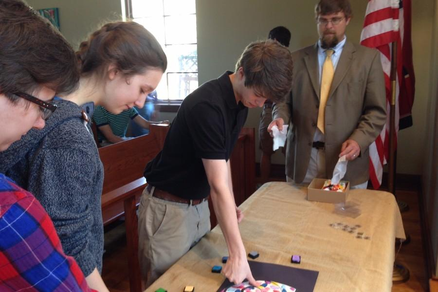 Cole+McLemore+stamps+his+fingerprint+on+the+art+piece+dedicated+for+the+seniors.+All+freshmen+through+seniors+participated+in+the+artistic+chapel+service.