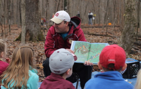 School President Bill Taylor reads to senior-kindergarten students at Dad's Day in the Woods. This is Mr. Taylor's last year at St. George's.