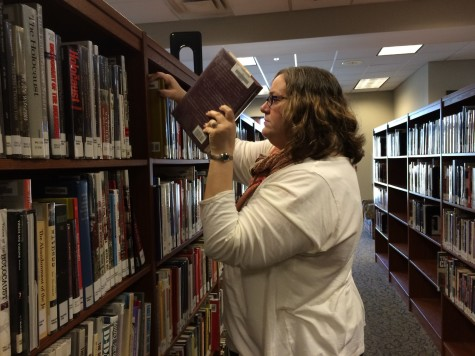 Mrs. Leah Allison works to improve the library by putting away a book that was put in the wrong spot, making it available for students to find easily. The library has been a fundamental part of the St. George's community since its founding, hosting a quiet place for studying and reading.