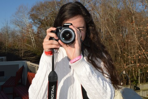 Senior Sophia Quesada poses for a photo while looking through her camera lens. For her SIS project she took photos of different students.