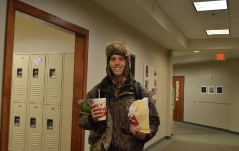Senior William McBride holds his Chick-fil-A while wearing camouflage. Wednesday's spirit week was hide and seek day, and freshmen and juniors wore neon while sophomores and seniors wore camouflage.