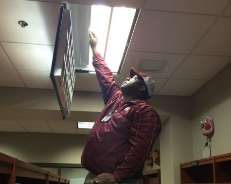Mr. Ricky fixes a lightbulb in the library. Mr. Ricky has been responsible for much of the maintenance that is needed within the school for two years.