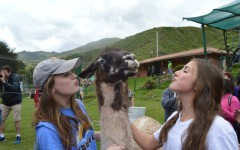 Freshmen Ann Wallace Scott and Kate Murphy kiss a llama at a local zoo in Peru. Students from the upper school ventured to Peru to partner with MedLife to bring medical care to low-income families.