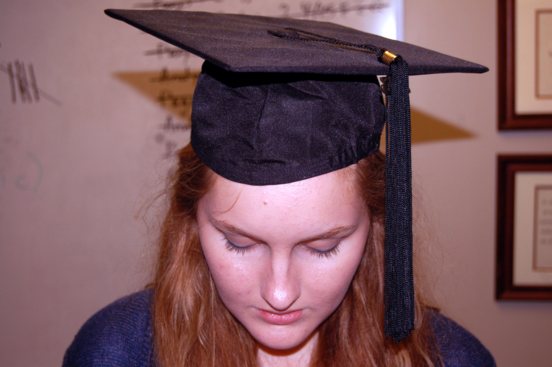 A student poses in a cap and gown. SIS alone determined graduation with distinction this year.