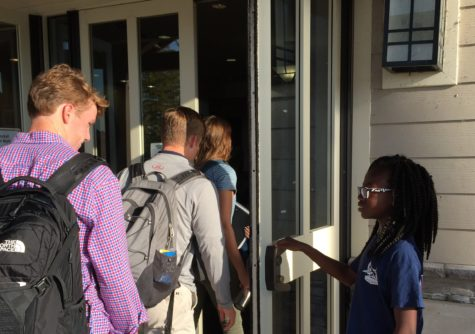 Sixth grader Erica Afenya holds the door for several juniors. Afenya started at the Germantown campus in fifth grade.