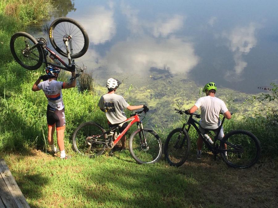 Team+founders+and+seniors+Kneeland+Gammill+and+J.D.+Hibner+gaze+over+Bulldog+Lake+after+a+ride+with+junior+Soren+Jensen.+The+new+mountain+bike+team+began+rides+at+the+end+of+August.