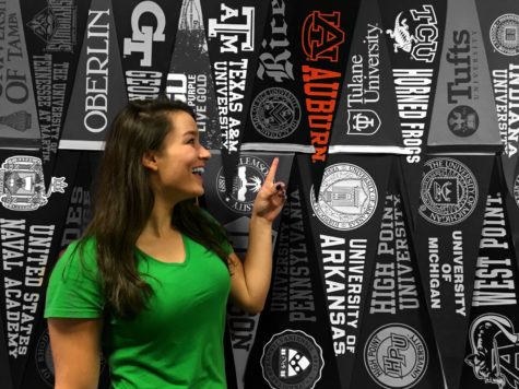 Junior Kate Seabrook points at an Auburn University banner. Some students have already decided which college they want to attend.