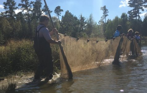 Juniors Nick Bourdeau, Griffin Gilliam, Lathan Spadafora and Parker Ruffin walk into the pond in their waders. The trip to Bulldog Pond coincided with the grade's introduction to the ecosystem.