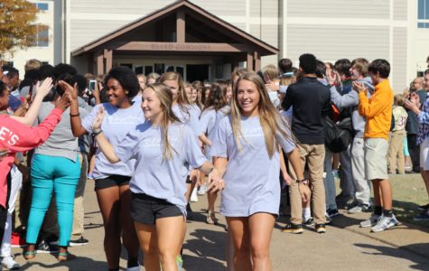 Seniors Eva Neel and Avery Whitehead lead the soccer team to the bus. The varsity soccer team won Friday, Oct. 21, which secured their spot in the state semifinals.