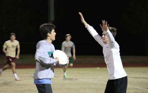 Junior Dalton Reese guards Ultimate Club president Winston Margaritis as he looks to throw downfield. The Ultimate Club held a game in the football stadium on Feb. 16.