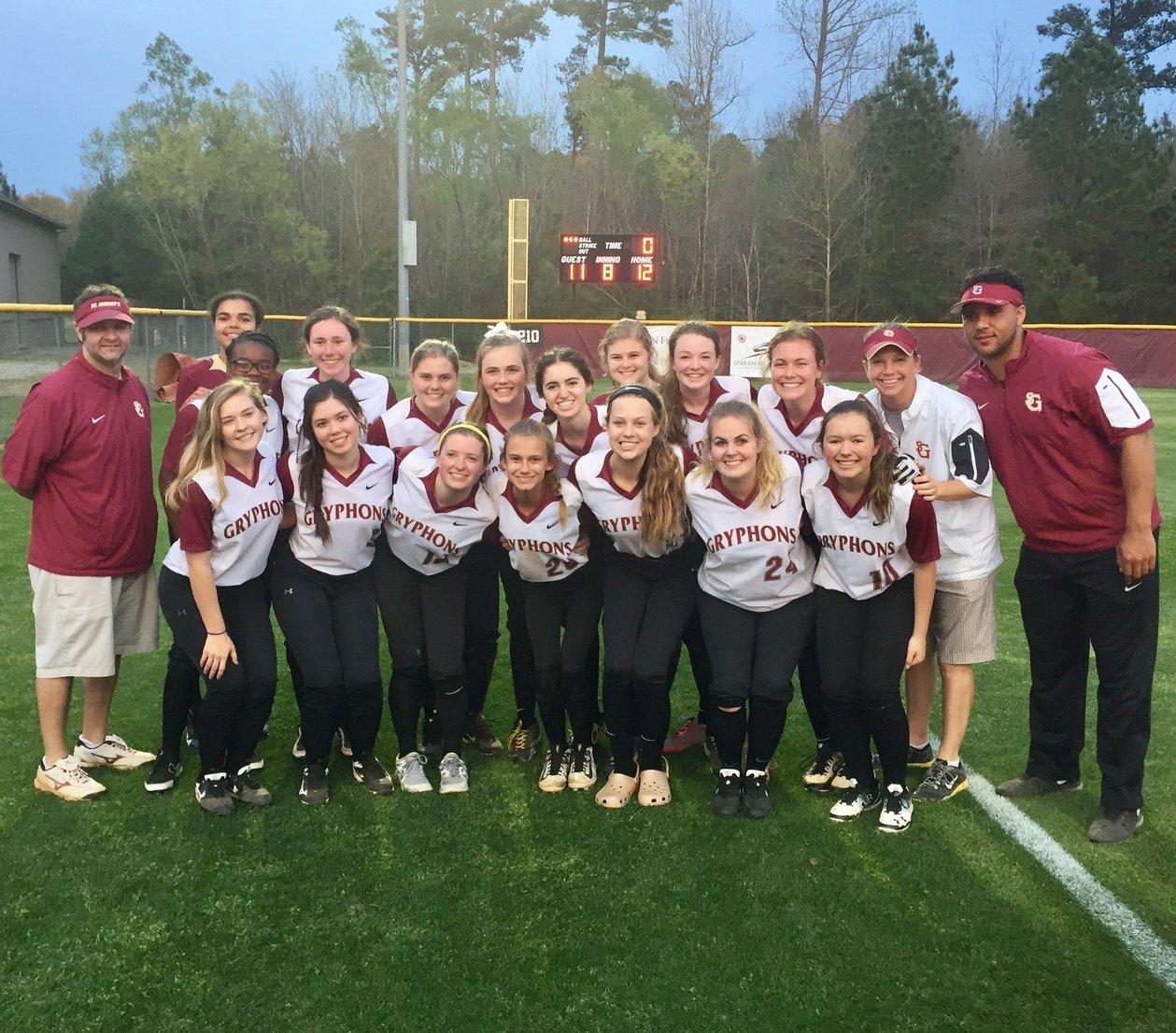 The softball team poses in front of the scoreboard after winning their game against the St. Agnes Stars. The 12-11 win was their first win of the season.