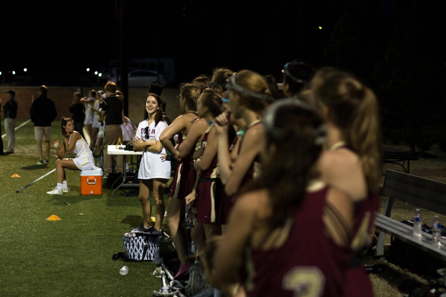 Junior Emily Grace Rodgers looks down the girls lacrosse team line during the game against Hutchison. Rodgers was unable to play lacrosse this season after receiving a concussion over a year ago.