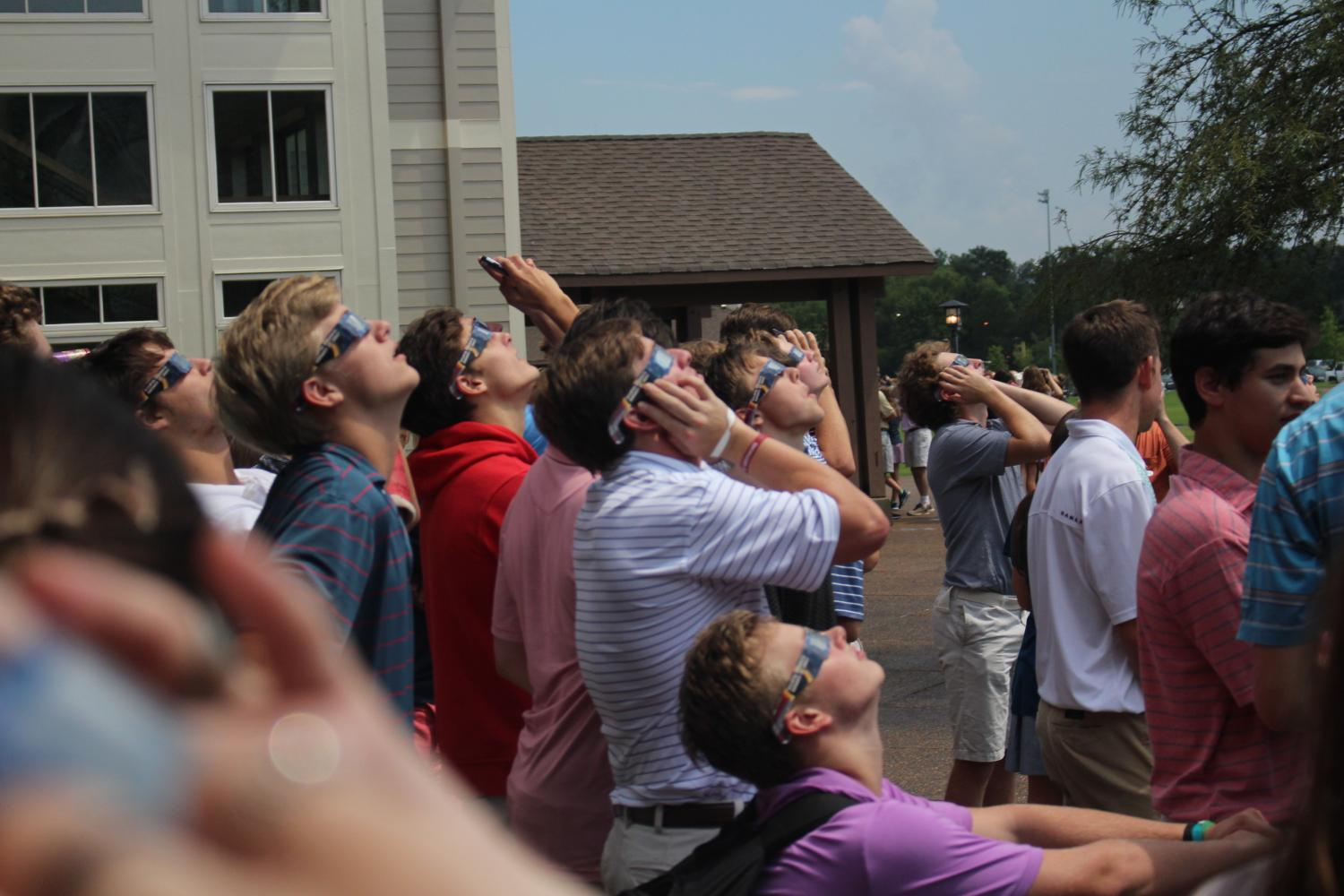 A+cluster+of+high+school+boys+gathers+to+view+the+eclipse+through+their+glasses.