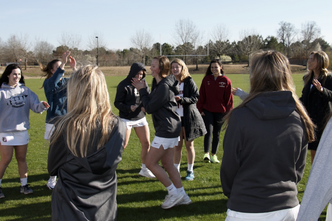 The girls lacrosse team dances before a practice. The team recently added Coach Rachel Smith to their staff.