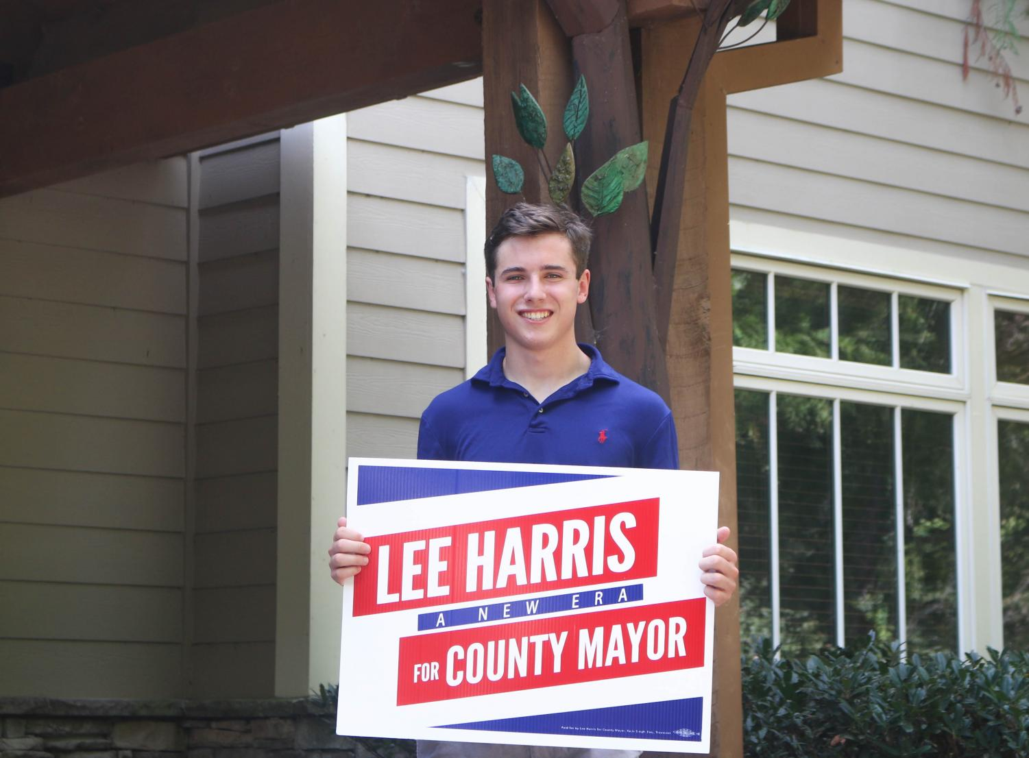 St. George's alumnus poses with a Lee Harris sign from the recent campaign. Doucette said the experience of working on the campaign helped him learn leadership skills.