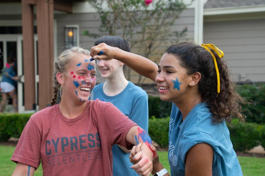 Senior Sara Washington paints Ironwood's blue on Cypress member and freshman Morgan Schrum. Paint-up was just one of the many activities available on House Day.
