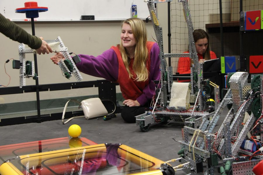 Junior+Elizabeth+Crane+smiles+as+she+receives+a+robot+base.+The+team+collaborated+on+the+field+while+preparing+for+the+tournament.