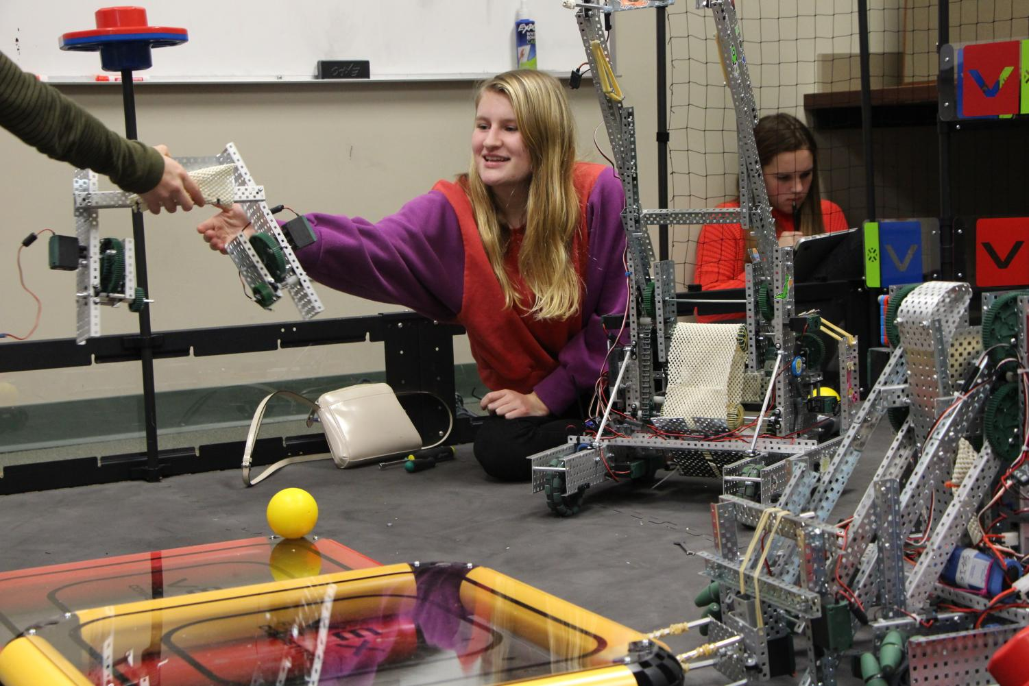 Junior Elizabeth Crane smiles as she receives a robot base. The team collaborated on the field while preparing for the tournament.