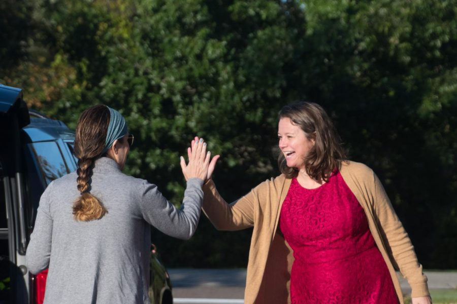 Ms. McCarthy high-fives a mom on High-Five Friday. Ms. McCarthy started the tradition with the intent to give students and families a boost of confidence to start the day.
