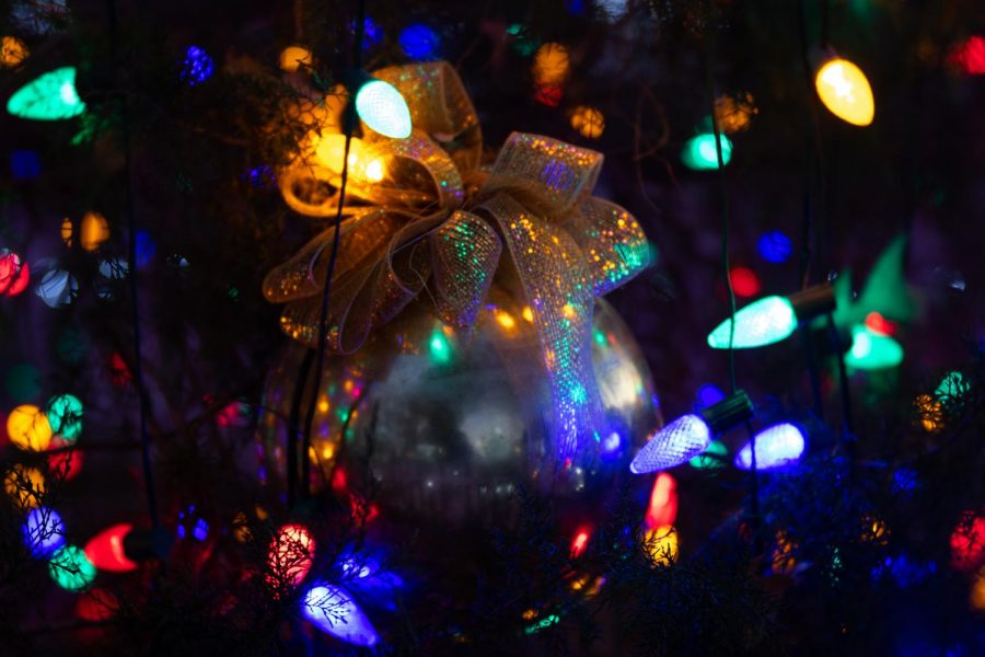 An fancy Christmas tree ornament dazzles from its Christmas tree. Ornaments are but one of the many traditions that surround Christmas trees.