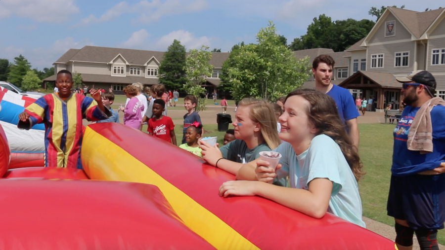 Sixth-grade students smile and eat snow cones as they watch their teacher jump on the bouncy house. They participated in the annual end of school carnival.