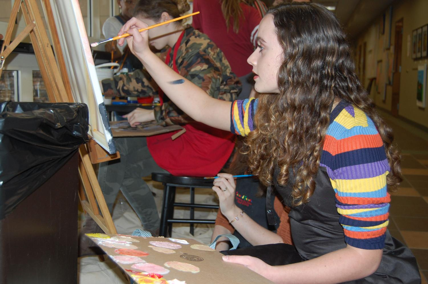 Student artist Chloe Lewis paints at the art show. This display was one of many student showcases.