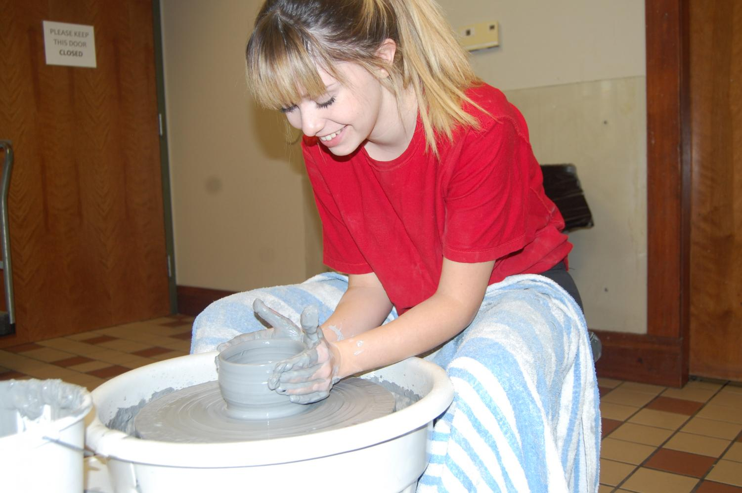 Senior Khai Willis leans over her pottery wheel while shaping a clay bowl. Willis volunteered to do a pottery showcase at the St. George's Art Show on family day.