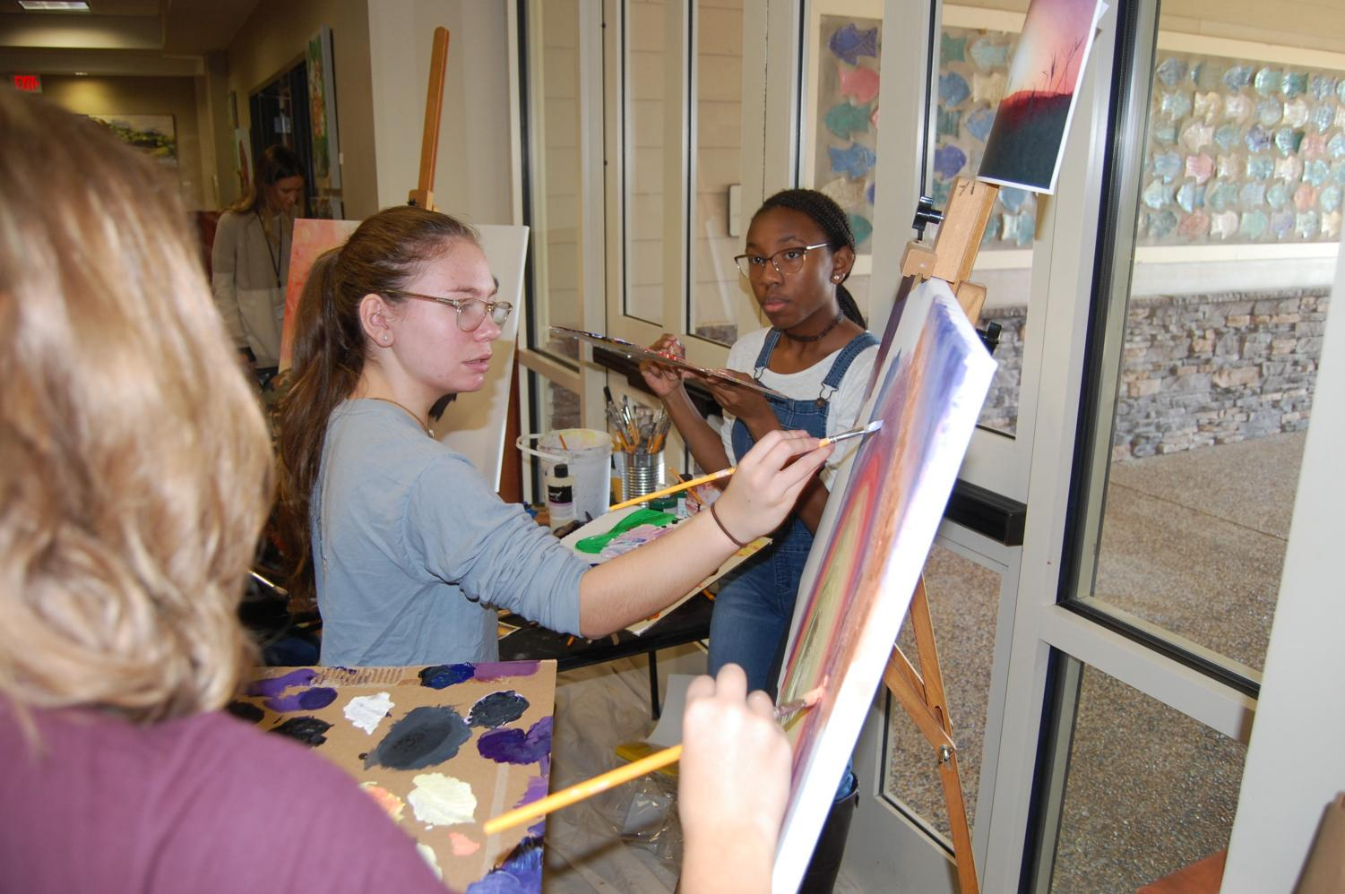 Sophomore Caroline Higley works with her group to paint a sunset at the Art Show on Nov 7. Two groups of students formed to work on the live art painting.