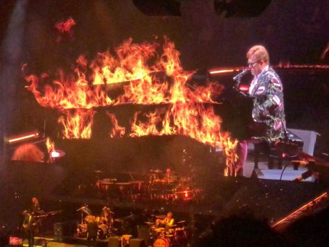 Elton John enthusiastically plays piano for his final Memphis audience. An effect on the screen shows his piano on fire.