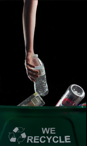 A student poses holding a water bottle over an overflowing recycling bin.