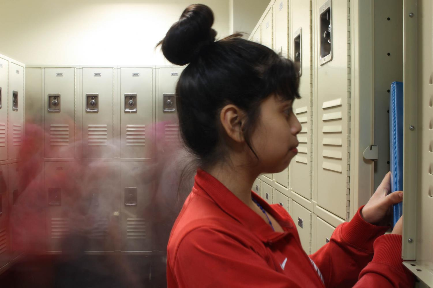 Eighth grader Jennifer Lopez poses looking through her locker. In the whirl of  everyday school life, students can feel overlooked.