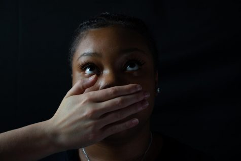 Junior Dariya Jones has a hand over her mouth, trying to cover up her words. In the article, Jones describes what she has the right to say.