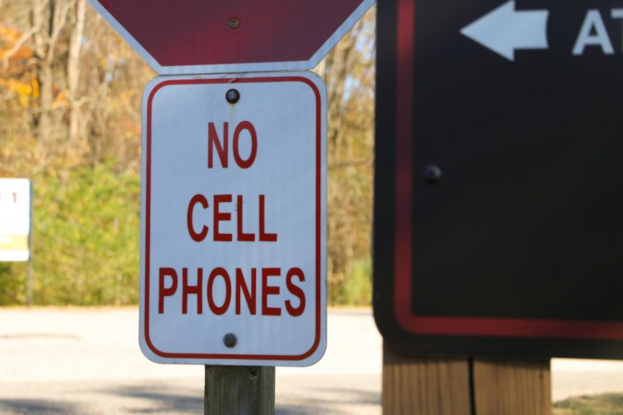 """A """"No Cell Phones"""" sign sits underneath the stop sign at the Houston Levee entrance to St. George"""