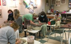 Mrs. Webb helps junior Joe Walters throw on the wheel. Mrs. Webb has faced many challenges this year with Pottery online. This class has become available to only in-person students now.