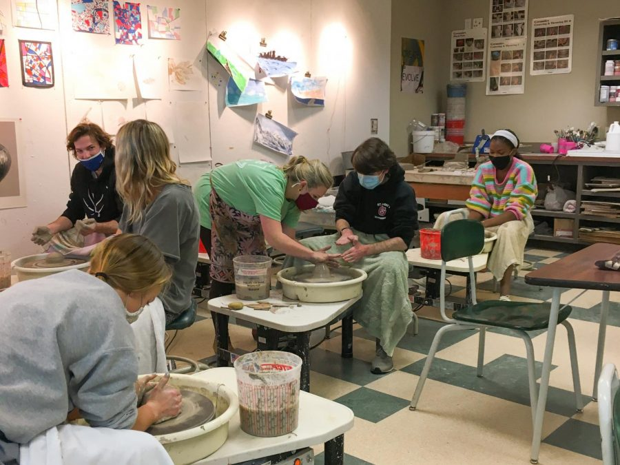 Mrs.+Webb+helps+junior+Joe+Walters+throw+on+the+wheel.+Mrs.+Webb+has+faced+many+challenges+this+year+with+Pottery+online.+This+class+has+become+available+to+only+in-person+students+now.