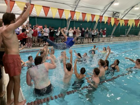 Choir teacher Mr. Nathan Dumser swan dives into the middle of a jubilant senior-filled pool.