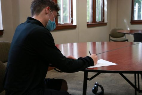 Freshman Dalton Lewis signs the permission slip for homecoming. Each student who is bringing an outside guest has to sign a permission slip.